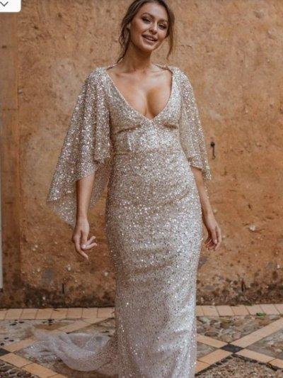 Изящное свадебное платье из легкого шифона. Акцент модели на открытом декольте в форме буквы V - притягивает взгляды к невесте. Топ, плечи и манжеты длинных рукавов выполнены в одном стиле - из ажурного кружева с геометрическим узором. Юбка не пышная, легкая. Прекрасный выбор для нежного образа невесты